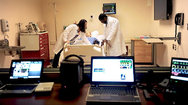 Adelphi nursing graduate students working with sim man