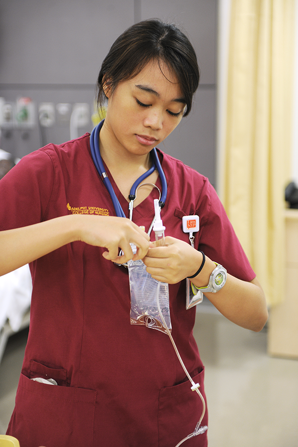 female Adelphi nursing student works with an IV